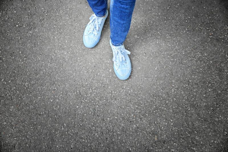 Πόδια της γυναίκας στα περιστασιακά παπούτσια στην άσφαλτο στοκ εικόνα