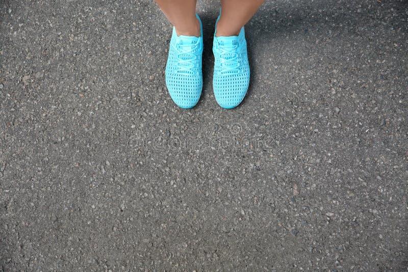 Πόδια της γυναίκας στα περιστασιακά παπούτσια στην άσφαλτο στοκ φωτογραφία με δικαίωμα ελεύθερης χρήσης