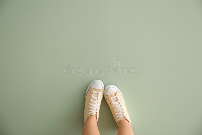 Πόδια της γυναίκας στα περιστασιακά παπούτσια στο υπόβαθρο χρώματος στοκ φωτογραφίες