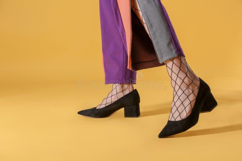 Πόδια της όμορφης νέας γυναίκας στα καλσόν και το παντελόνι στο υπόβαθρο χρώματος στοκ εικόνες με δικαίωμα ελεύθερης χρήσης