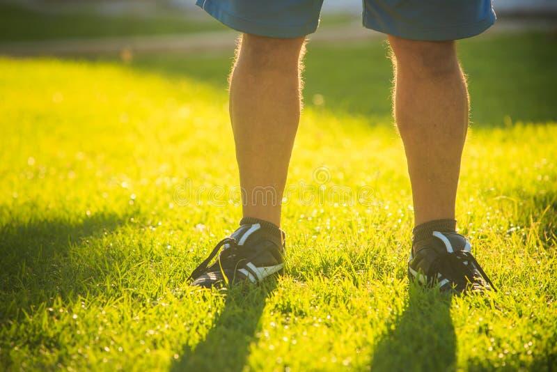 Πόδια του ατόμου στον ηλιόλουστο πράσινο χορτοτάπητα χλόης στοκ εικόνα με δικαίωμα ελεύθερης χρήσης