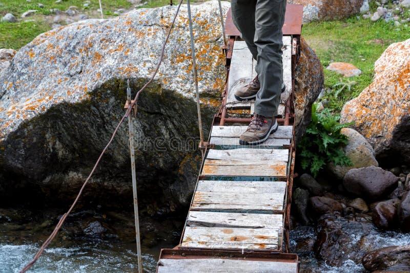 Πόδια του οδοιπόρου στη στενή ξύλινη γέφυρα πέρα από τον ποταμό βουνών στοκ εικόνες