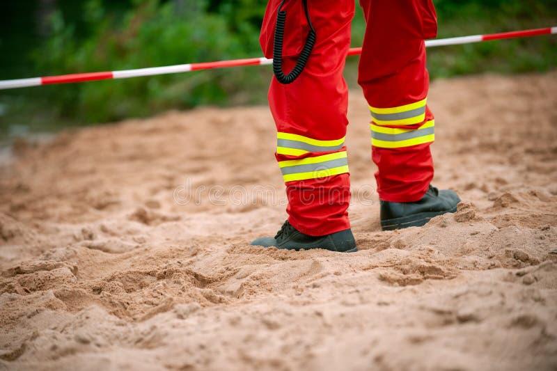 Πόδια του σωτήρα standind στην άμμο μπροστά από την κόκκινη και άσπρη ταινία στοκ φωτογραφία με δικαίωμα ελεύθερης χρήσης