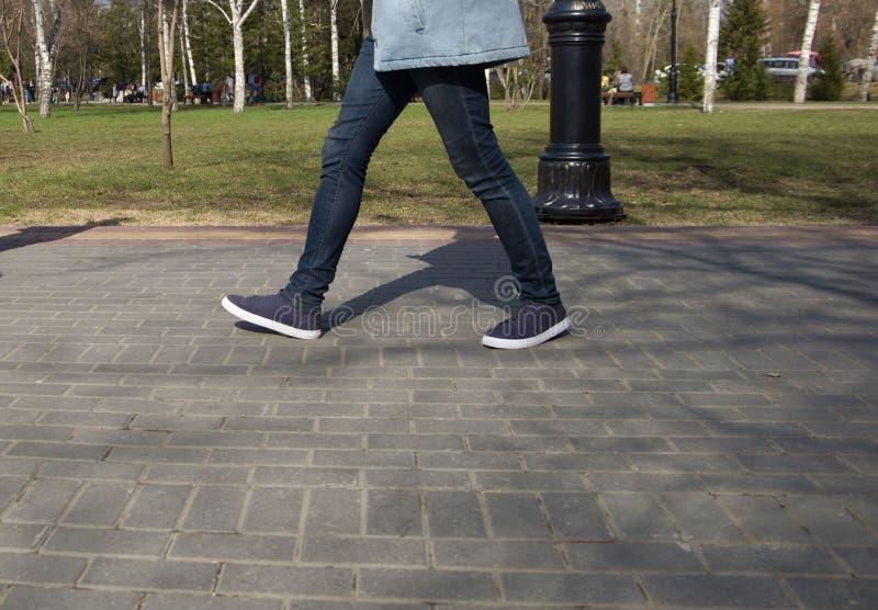 Πόδια των ανθρώπων που περπατούν στα αθλητικά παπούτσια κάτω από την οδό μια ηλιόλουστη ημέρα στοκ εικόνες