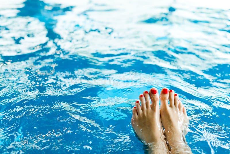 Πόδι γυναίκας με το κόκκινο pedicure στη λίμνη - toe στοκ εικόνες