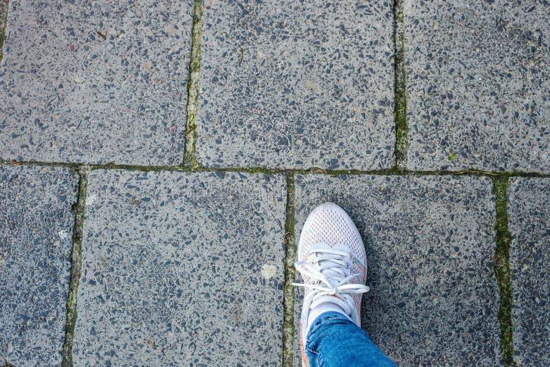 Πόδι γυναίκας στα άσπρα βήματα πάνινων παπουτσιών στην οδική τοπ άποψη στοκ εικόνες