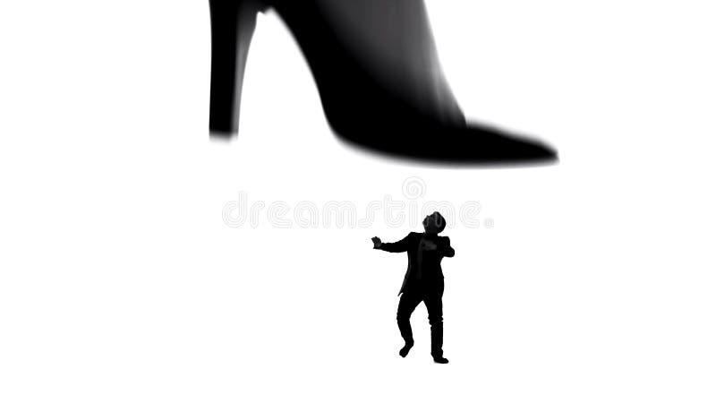 Πόδι γυναίκας στα υψηλά τακούνια που περπατούν στο μικρό αδύνατο άνδρα, θηλυκή εξουσίαση στο ζεύγος στοκ εικόνα