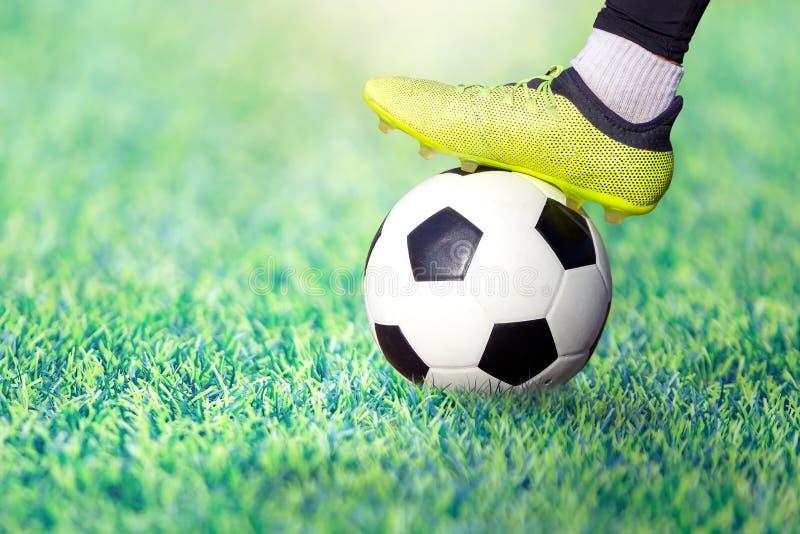 Πόδι ενός ποδοσφαιριστή σε μια μπότα ποδοσφαίρου σε μια σφαίρα σε έναν πράσινο χορτοτάπητα του σταδίου στοκ εικόνα με δικαίωμα ελεύθερης χρήσης