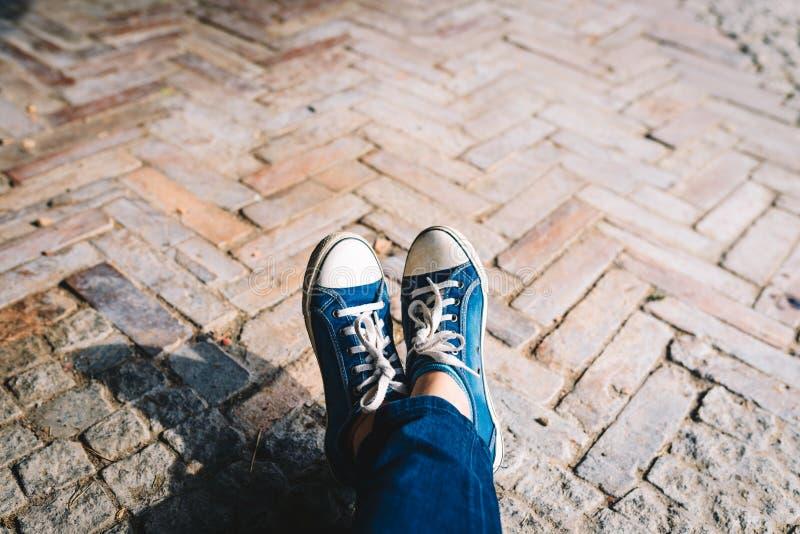 Πόδι και πόδια που βλέπουν άνωθεν σε ένα τούβλο, αγροτικό υπόβαθρο Selfie των πάνινων παπουτσιών στο πάτωμα στοκ εικόνες με δικαίωμα ελεύθερης χρήσης
