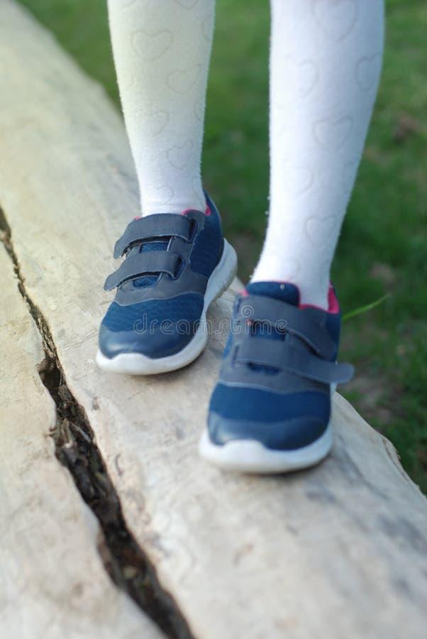 Πόδι κοριτσάκι στις αθλητικές μπότες που περπατούν στο ξύλο Πηγαίνοντας μέλλον TU Parenting και εκπαιδευτικός στοκ εικόνα