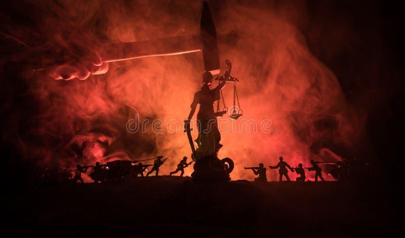 Πόλεμος - καμία έννοια δικαιοσύνης Στρατιωτικές σκιαγραφίες που παλεύουν τη σκηνή και το άγαλμα της δικαιοσύνης σε ένα σκοτεινό τ στοκ εικόνες