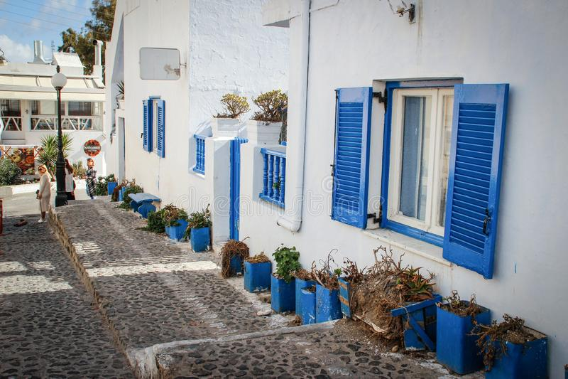 Πόλης οδός Fira με τους Λευκούς Οίκους και τα μπλε κλείνω με παντζούρια παράθυρα στοκ εικόνα με δικαίωμα ελεύθερης χρήσης