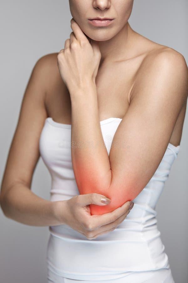 Πόνος αγκώνων Όμορφο θηλυκό σώμα κινηματογραφήσεων σε πρώτο πλάνο με τον πόνο στα όπλα στοκ εικόνες