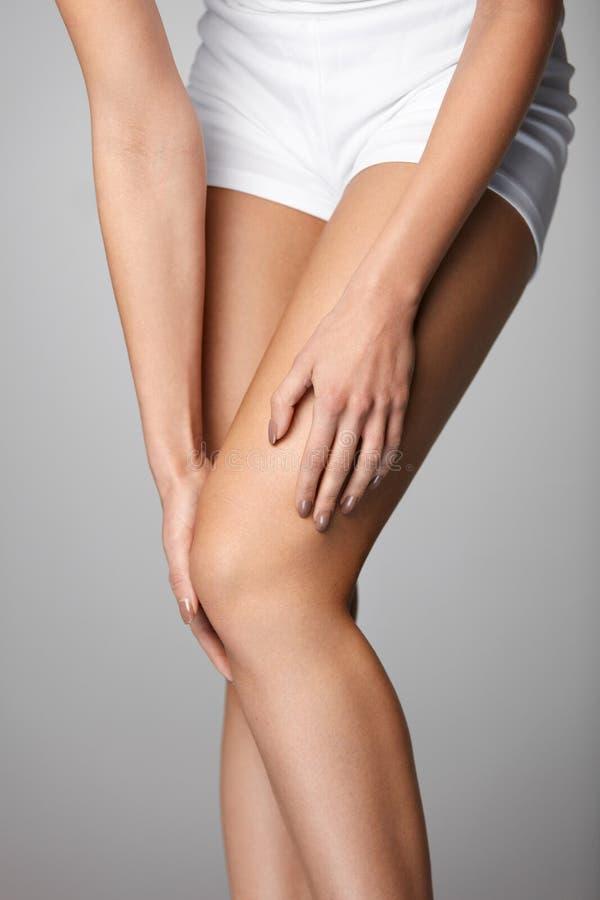 πόνος γονάτων Κινηματογράφηση σε πρώτο πλάνο του θηλυκού ποδιού με το επίπονο συναίσθημα στο γόνατο στοκ εικόνες