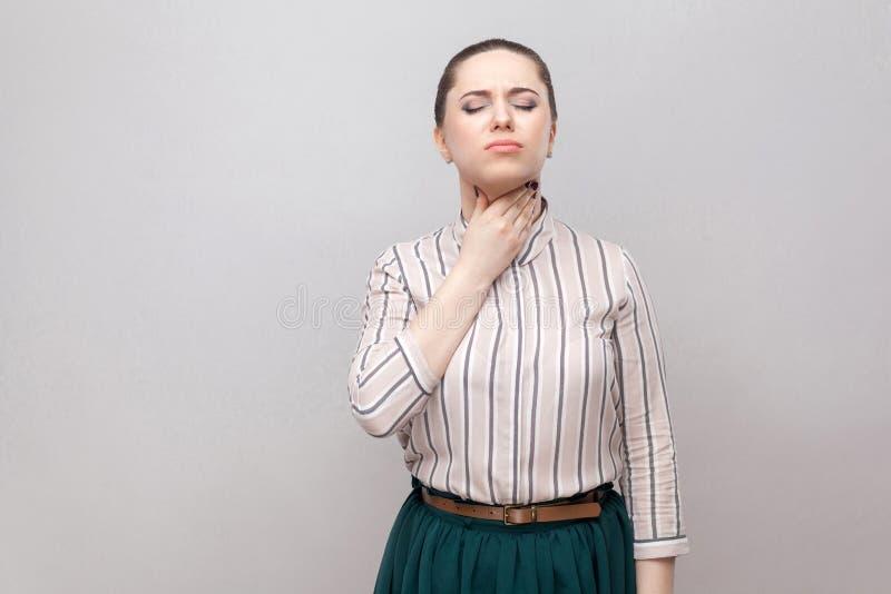 Πόνος λαιμού Πορτρέτο της άρρωστης όμορφης νέας γυναίκας στο ριγωτό πουκάμισο, την πράσινη φούστα και τη συλλεχθείσα απαγόρευση h στοκ εικόνα με δικαίωμα ελεύθερης χρήσης