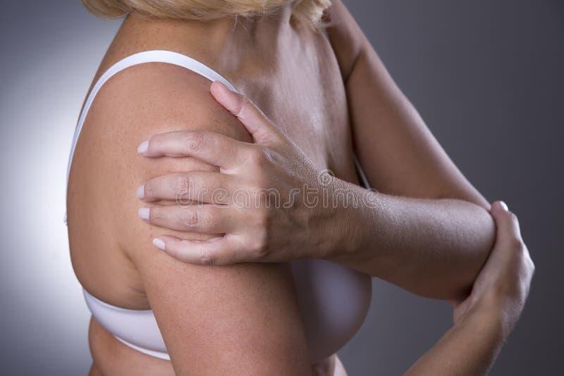 Πόνος στον ώμο, προσοχή των θηλυκών χεριών, πόνος στο σώμα γυναικών ` s στοκ εικόνες
