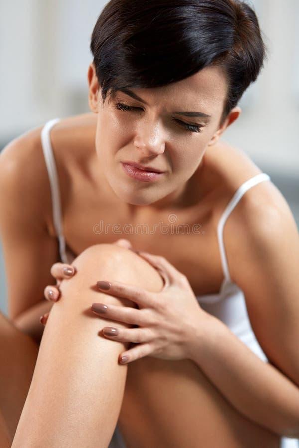 Πόνος σώματος Όμορφη γυναίκα με το επίπονο γόνατο, που αισθάνεται τον πόνο ποδιών στοκ εικόνα με δικαίωμα ελεύθερης χρήσης