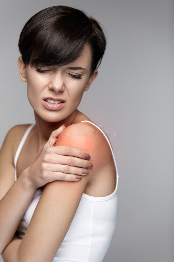 Πόνος σώματος Όμορφη γυναίκα που αισθάνεται τον πόνο στους ώμους και τα όπλα στοκ εικόνα με δικαίωμα ελεύθερης χρήσης