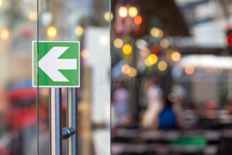 Πόρτα γυαλιού με ένα βέλος σε ένα εστιατόριο στοκ εικόνα