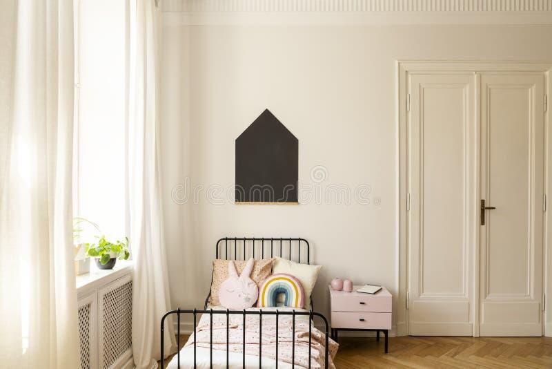 Πόρτα και γραφείο δίπλα στο κρεβάτι με τα ζωηρόχρωμα μαξιλάρια στην κρεβατοκάμαρα του παιδιού στοκ φωτογραφία με δικαίωμα ελεύθερης χρήσης