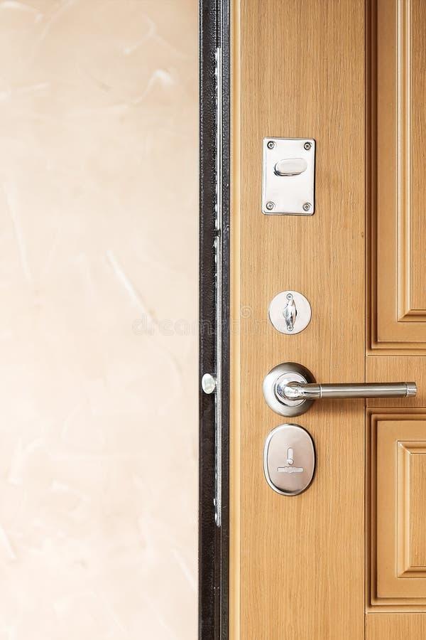 Πόρτα μετάλλων με το κλείδωμα Σύγχρονη λαβή πορτών ύφους στη φυσική ξύλινη πόρτα στοκ φωτογραφίες