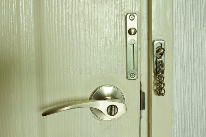 Πόρτα με τη λαβή και κλειδωμένη αλυσίδα στεφανών στο σπίτι στοκ εικόνες