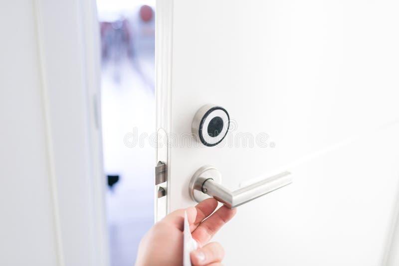 Πόρτα ξενοδοχείων - νεαρός άνδρας που κρατά ένα keycard μπροστά από τον ηλεκτρονικό αισθητήρα μιας πόρτας δωματίων Ταξίδι ή επιχε στοκ φωτογραφίες με δικαίωμα ελεύθερης χρήσης