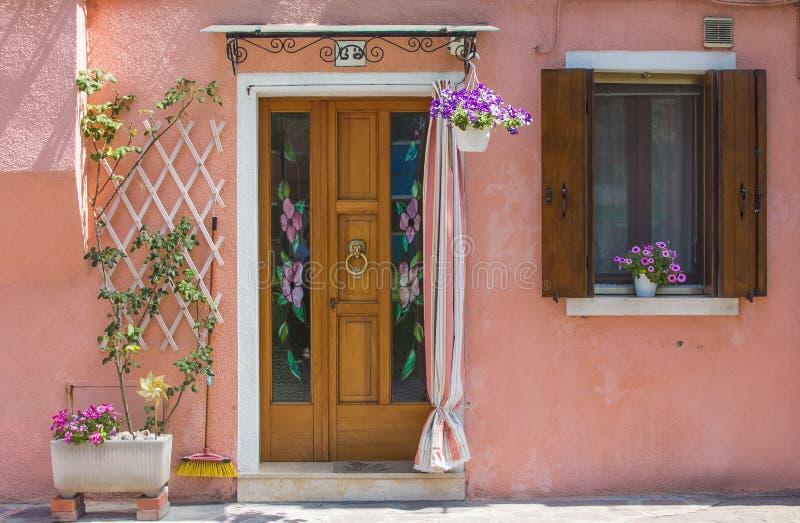 Πόρτα του ρόδινου σπιτιού με τα λουλούδια στοκ εικόνες