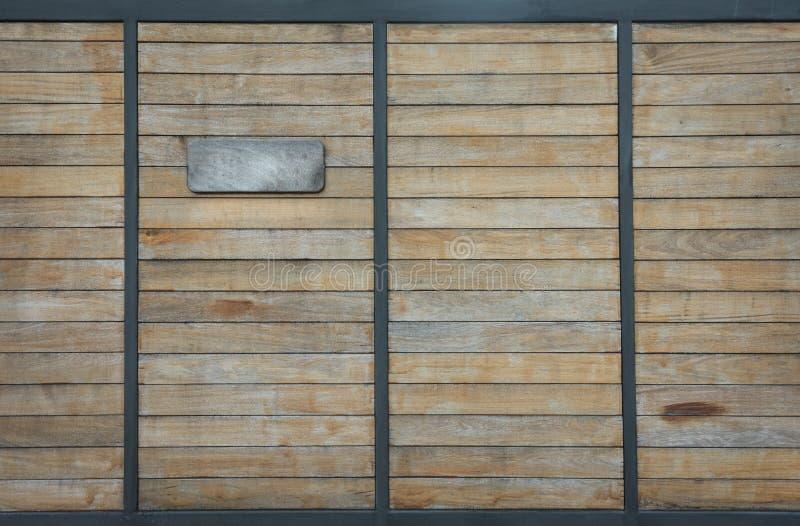 Πόρτα φωτογραφικών διαφανειών ξύλου και χάλυβα με την ετικέτα του αριθμού σπιτιών στοκ φωτογραφία με δικαίωμα ελεύθερης χρήσης