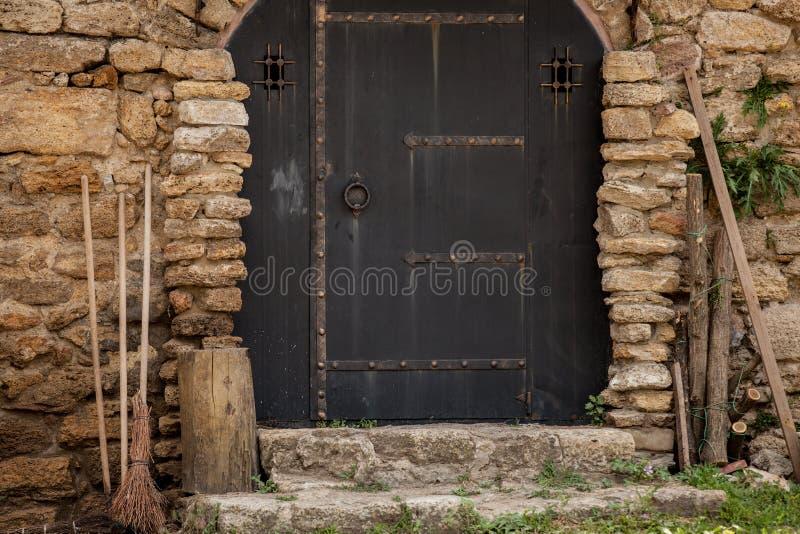 Πόρτες με τη σκούπα και ξύλα στο φρούριο τουβλότοιχος στοκ φωτογραφία με δικαίωμα ελεύθερης χρήσης