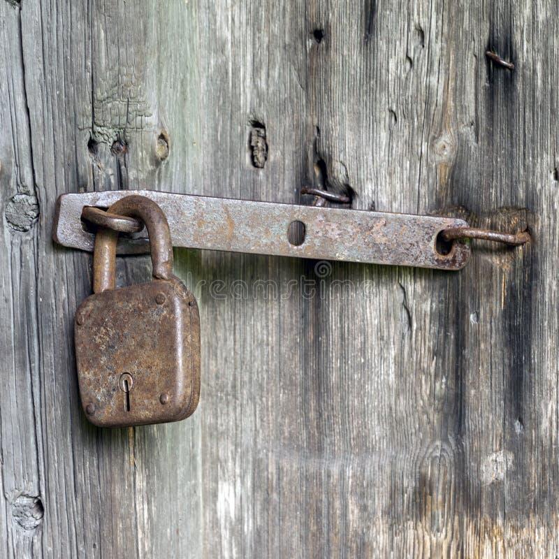 Πόρτες που κλειδώνονται με το σκουριασμένο λουκέτο στοκ εικόνα
