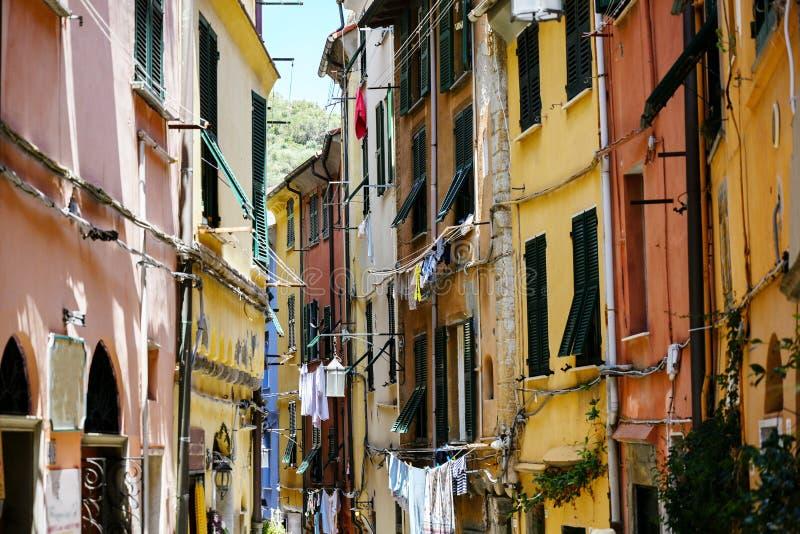 Πόρτο Venere στην Ιταλία, χαρακτηριστική στενή παλαιά πόλης οδός με τα ζωηρόχρωμες σπίτια και τις σκοινιά για άπλωμα στοκ εικόνες
