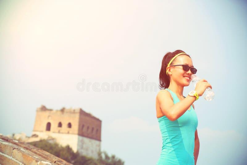 Πόσιμο νερό αθλητών δρομέων γυναικών στο κινεζικό Σινικό Τείχος στοκ εικόνες