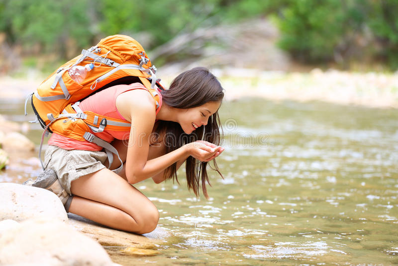 Πόσιμο νερό γυναικών οδοιπόρων από την πεζοπορία κολπίσκου ποταμών στοκ εικόνα με δικαίωμα ελεύθερης χρήσης