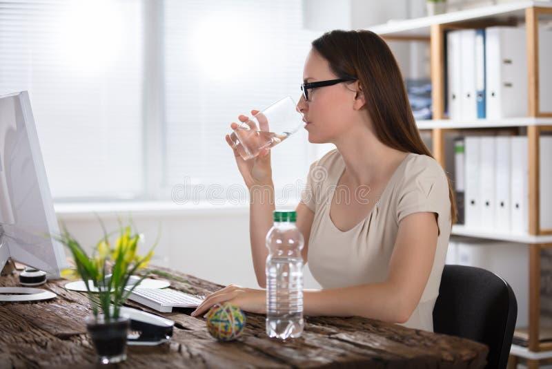Πόσιμο νερό γυναικών χρησιμοποιώντας τον υπολογιστή στοκ φωτογραφία