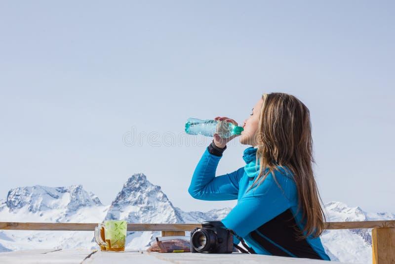Πόσιμο νερό γυναικών snowboarder υπαίθρια σε ένα κλίμα ο στοκ εικόνες