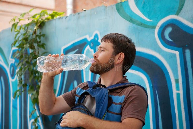 Πόσιμο νερό νεαρών άνδρων από τα πλαστικά μπουκάλια στο υπόβαθρο με τα γκράφιτι στοκ εικόνες