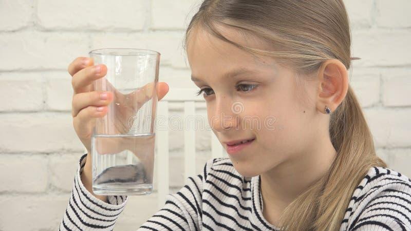 Πόσιμο νερό παιδιών, διψασμένο παιδί που μελετά το γυαλί του γλυκού νερού, κορίτσι στην κουζίνα στοκ εικόνα