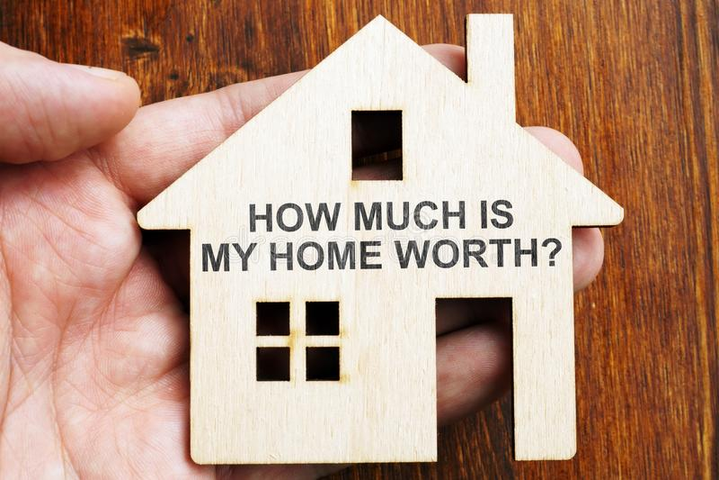 Πόσο είναι το σπίτι μου αξίας; Σημάδι στο πρότυπο του σπιτιού στοκ φωτογραφία με δικαίωμα ελεύθερης χρήσης