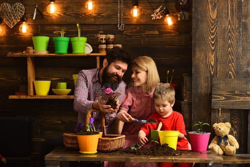 Πότισμα προσοχής λουλουδιών Εδαφολογικά λιπάσματα ευτυχείς κηπουροί με τα λουλούδια άνοιξη φύση αγάπης παιδιών γυναικών, ανδρών κ στοκ εικόνα με δικαίωμα ελεύθερης χρήσης