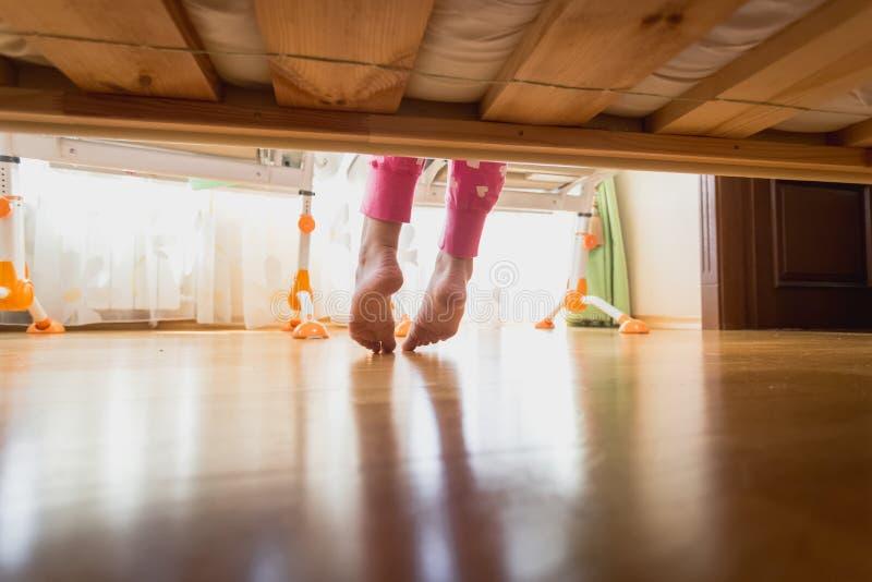 Πόδια έφηβη κάτω από το κρεβάτι στο πρωί στοκ εικόνα