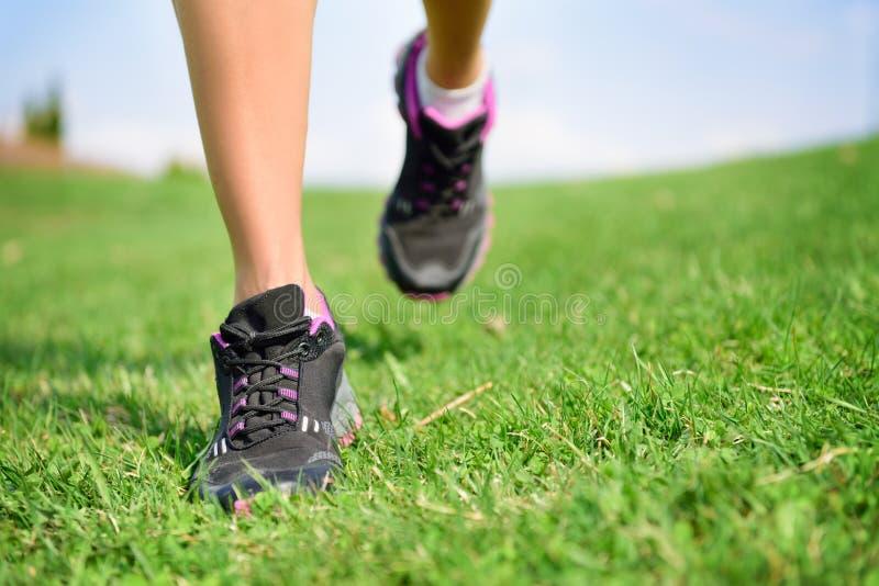 Πόδια αθλητών δρομέων που τρέχουν στη γυναίκα ικανότητας χλόης στοκ φωτογραφίες με δικαίωμα ελεύθερης χρήσης