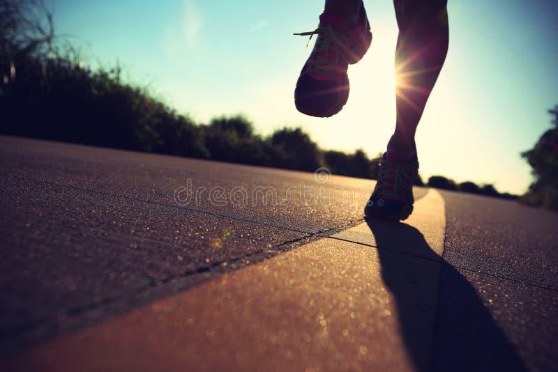 Πόδια αθλητών δρομέων που τρέχουν στο δρόμο παραλιών στοκ εικόνα με δικαίωμα ελεύθερης χρήσης