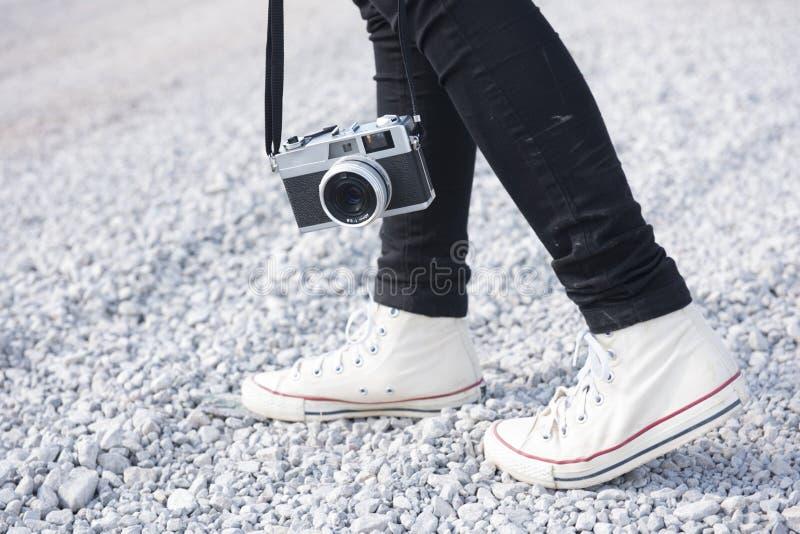 Πόδια ατόμων και εκλεκτής ποιότητας αναδρομικός τρόπος ζωής ταξιδιού καμερών φωτογραφιών υπαίθριος στοκ εικόνα