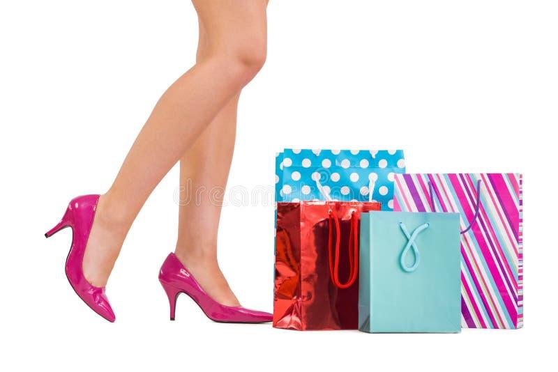 Πόδια γυναίκας στα υψηλά τακούνια με τις τσάντες αγορών στοκ φωτογραφίες