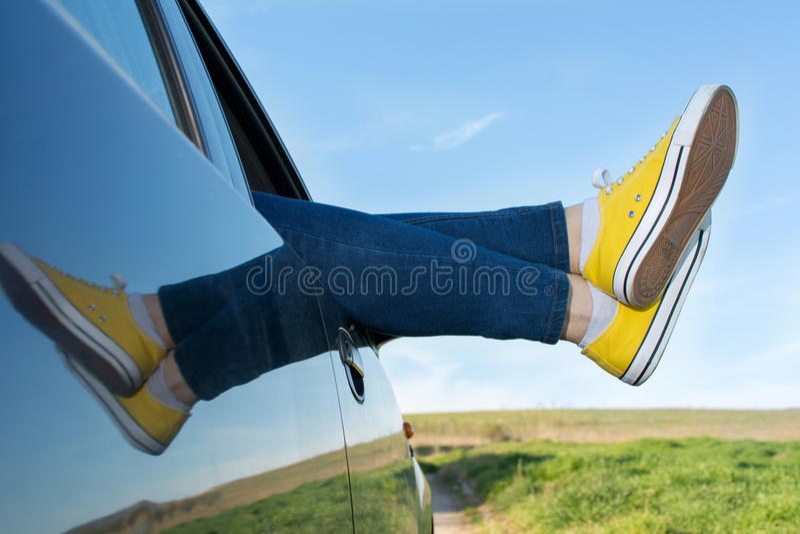 Πόδια γυναικών από το παράθυρο αυτοκινήτων στοκ εικόνα με δικαίωμα ελεύθερης χρήσης