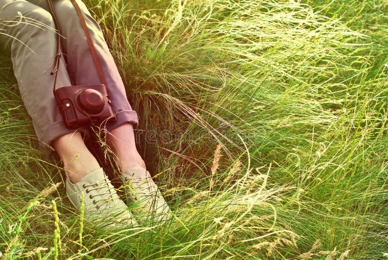 Πόδια γυναικών και εκλεκτής ποιότητας αναδρομική κάμερα φωτογραφιών υπαίθρια στοκ φωτογραφίες