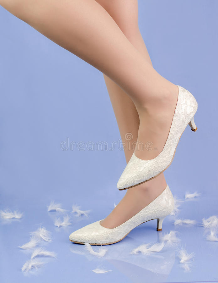 Πόδια γυναικών με τα κλασικά άσπρα παπούτσια στοκ φωτογραφίες