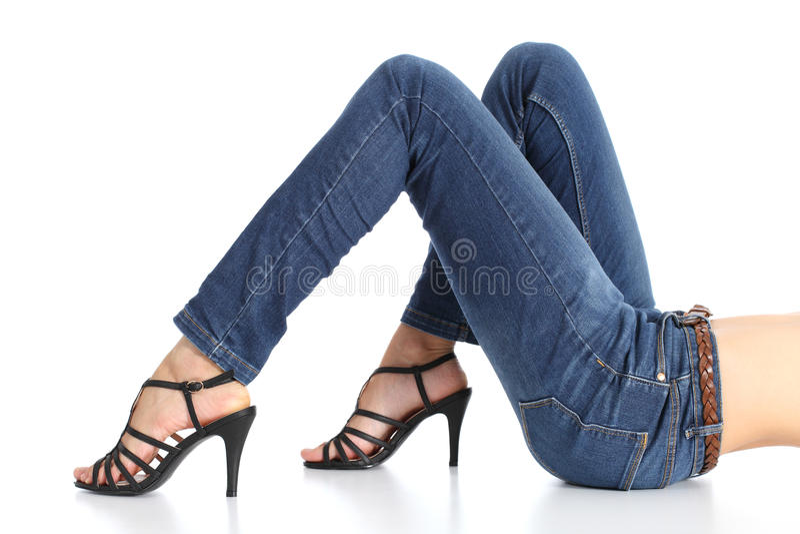 Πόδια γυναικών με τα τζιν και τακούνια σανδαλιών που απομονώνονται στοκ εικόνες