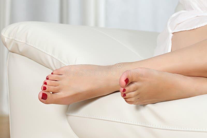 Πόδια γυναικών με το κόκκινο pedicure σε έναν καναπέ στοκ εικόνα